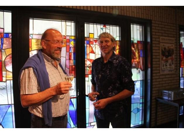 Kunstenaar-glazenier Jules Claes (links) ontwierp op vraag van de parochie Bret-Gelieren, een glas in loodraam in de te renoveren inkomhal van de Fatima Kerk. Afgelopen zondag werd het raam, na de ochtendmis, ingehuldigd met een kleine receptie. Rechts: Felicien Penders, vriend en collega-glazenier van Jules Claes en mede-uitvoerder van het kunstwerk.